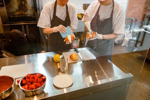 Confeiteiros de aventais enchem pão fresco com creme em uma padaria moderna