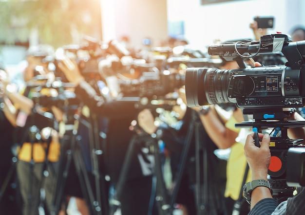Conferência de imprensa. câmera de vídeo no grupo borrada de imprensa e mídia fotógrafo