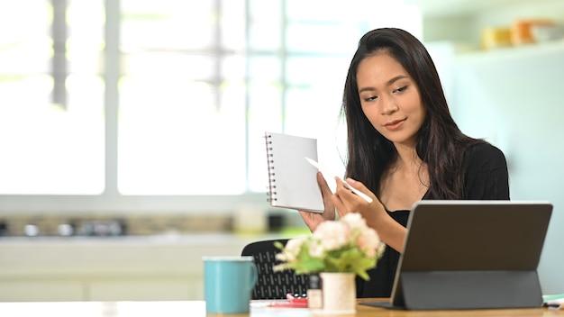 Conferência de jovem empresária asiática de colegas através de um tablet.