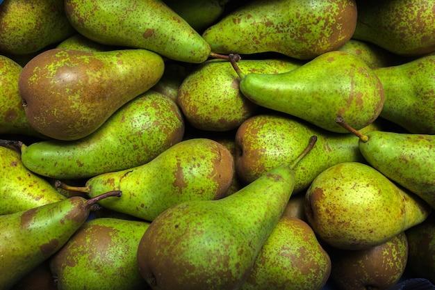 Conferência de peras frescas à vela no mercado de vegetais