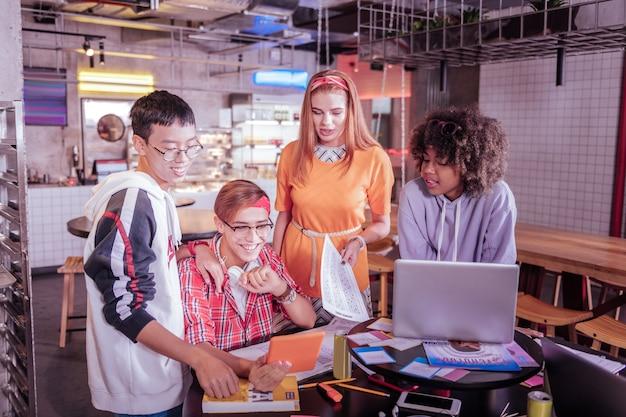 Conferência online. alunos satisfeitos e positivos olhando para o gadget enquanto estudam juntos