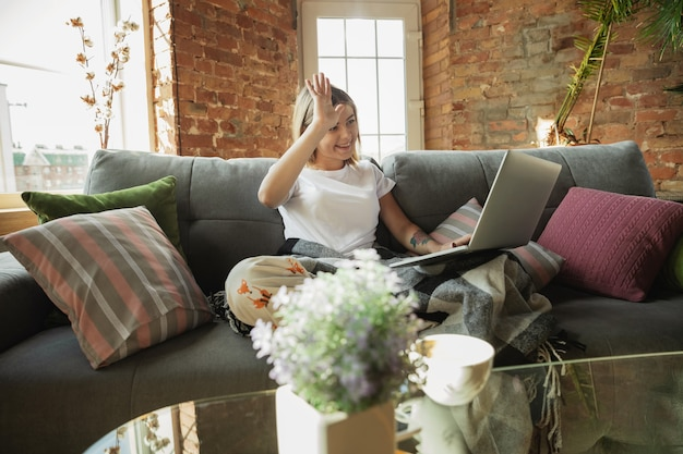 Conferência online. mulher caucasiana, freelancer durante o trabalho em home office durante a quarentena. jovem empresária em casa, auto-isolada. usando gadgets. trabalho remoto, prevenção de disseminação de coronavírus.