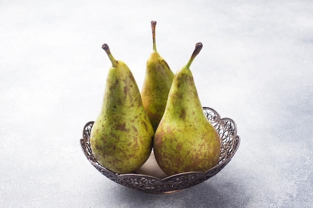 Conferência suculenta fresca das peras em uma cesta em um fundo cinzento.