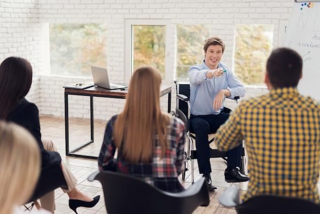 Conferencista em cadeira de rodas na frente do público das pessoas.