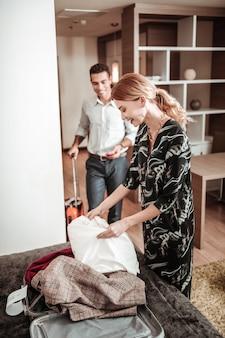 Conferindo. linda esposa loira com rabo de cavalo fazendo a mala durante o check-out do hotel