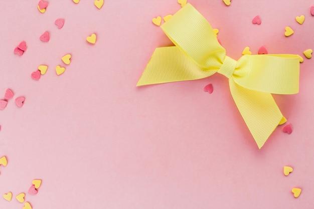 Confete confeitaria em forma de coração amarelo e rosa e laço amarelo em um espaço de cópia de fundo rosa
