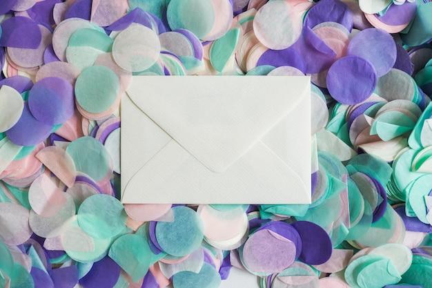 Confete de cor pastel vista superior com envelope no meio