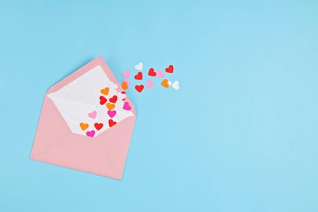 Confete de corações e envelope rosa.