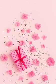Confete de glitter dourados de caixa de presente e flores no espaço da cópia de férias rosa