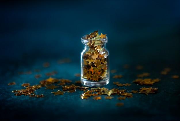 Confete de glitter dourados na pequena garrafa de vidro