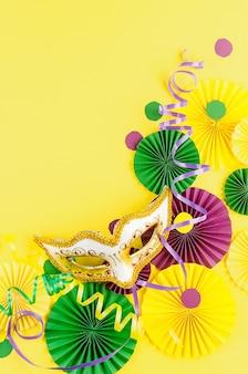 Confete de papel colorido, máscara de carnaval e serpentina colorida em um fundo amarelo