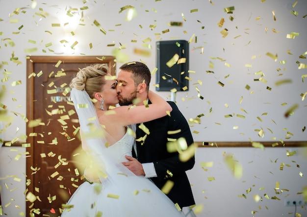 Confete dourado cair beijando o casal de noivos