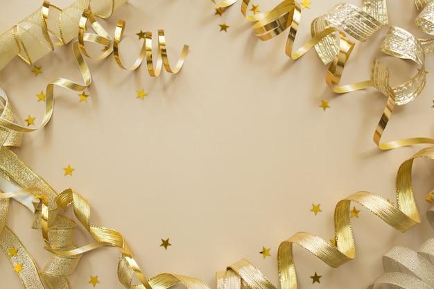 Confete dourado, fitas em fundo bege. composição de natal. cenário de férias festivas.