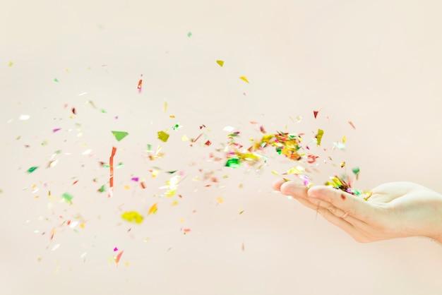Confete soprando das mãos contra o fundo bege