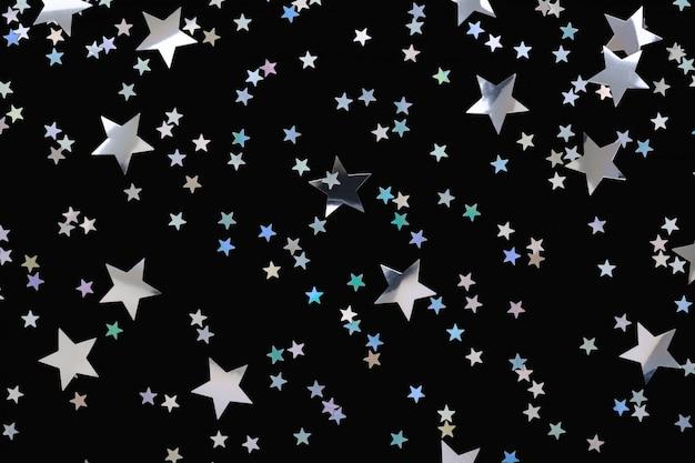 Confetes caindo de estrelas de prata sobre fundo preto