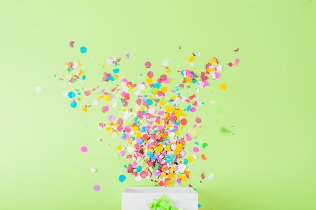 Confetes coloridos caindo na caixa branca sobre o pano de fundo verde