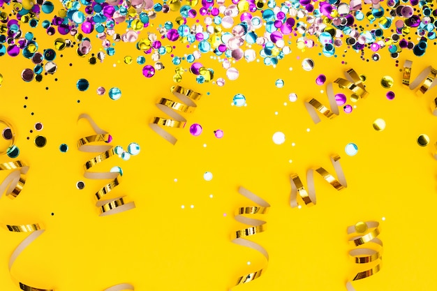 Confetes coloridos e serpentinas enroladas douradas fundo amarelo