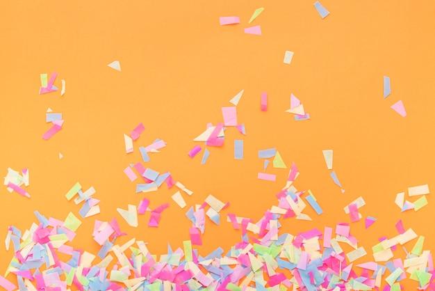 Confetes coloridos em um fundo laranja