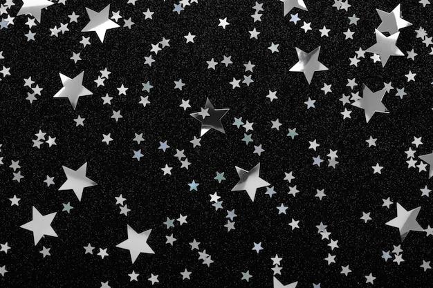 Confetes de estrelas de prata sobre fundo preto férias festivas glitter brilha.