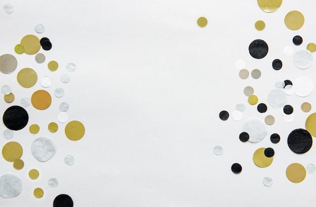 Confetes de ouro, prata, preto e branco