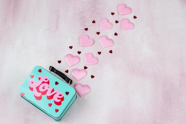 Confetes e corações rosa voam para fora da caixa