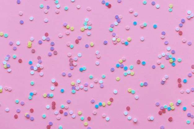 Confetes em fundo rosa pastel, feriados de comemoração de ano novo de aniversário