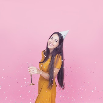 Confetes, queda, sobre, a, sorrindo, mulher jovem, segurando, flauta champanha