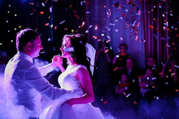 Confetti cair no casal de noivos girando na fumaça