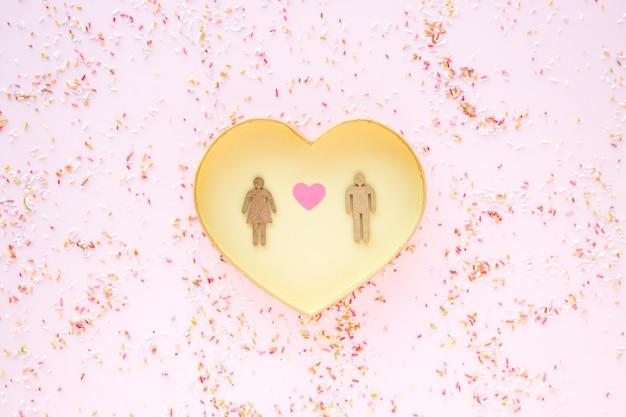 Confetti em torno do coração com casal heterossexual
