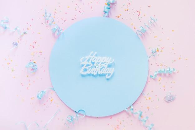 Confetti um flâmulas em torno de escrita de aniversário