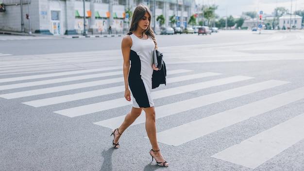Confiança feminina. independência. mulher poderosa bem sucedida atravessando a rua urbana.