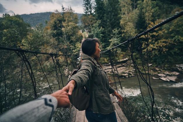 Confiança real. mulher jovem e bonita de mãos dadas com o namorado enquanto caminha na ponte pênsil