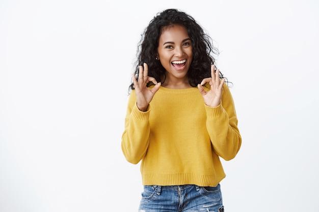 Confiante alegre jovem sortuda com penteado encaracolado, mostre-se bem, aceitando o gesto sorrindo feliz, satisfeita com ótimo resultado incrível, julgando filme legal, parede branca