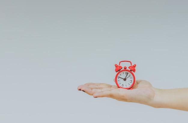 Confiante amigável jovem, mulher caucasiana, segurando um grande relógio nas mãos, mostrando o sucesso e a alegria do bom horário do escritório em um conceito de happy hour