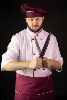 Confiante chef barbudo homem de uniforme detém duas facas cruzando-os