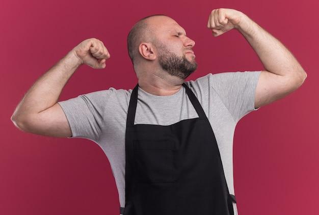 Confiante com os olhos fechados, barbeiro de meia-idade de uniforme, mostrando forte gesto isolado na parede rosa