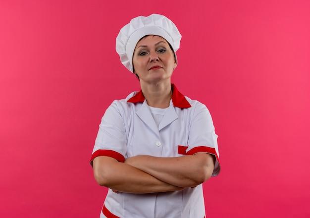 Confiante cozinheira de meia-idade com uniforme de chef, cruzando as mãos na parede rosa isolada com espaço de cópia