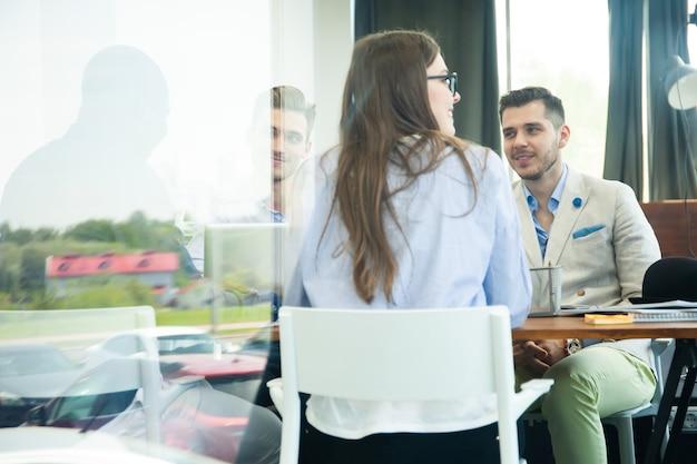 Confiante e bem-sucedido. jovens colegas modernos em roupas casuais inteligentes, trabalhando enquanto passam o tempo no escritório.