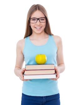 Confiante e inteligente. adolescente alegre segurando uma pilha de livros com uma maçã e sorrindo enquanto fica de pé, isolado no branco