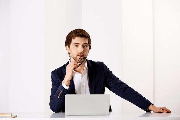 Confiante, elegante empresário de terno, sente-se a mesa de escritório perto de laptop, pensativo