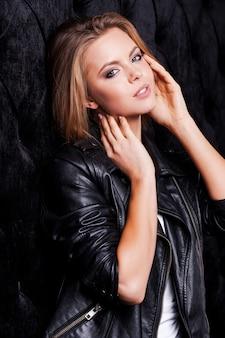 Confiante em seu estilo. mulher jovem e bonita em uma jaqueta de couro posando contra um fundo preto
