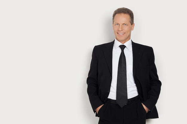 Confiante em si mesmo. homem maduro alegre em trajes formais de mãos dadas nos bolsos e sorrindo em pé contra um fundo cinza