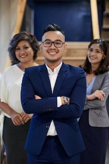 Confiante empresário asiático posando com braços cruzados e duas colegas femininas em pé atrás