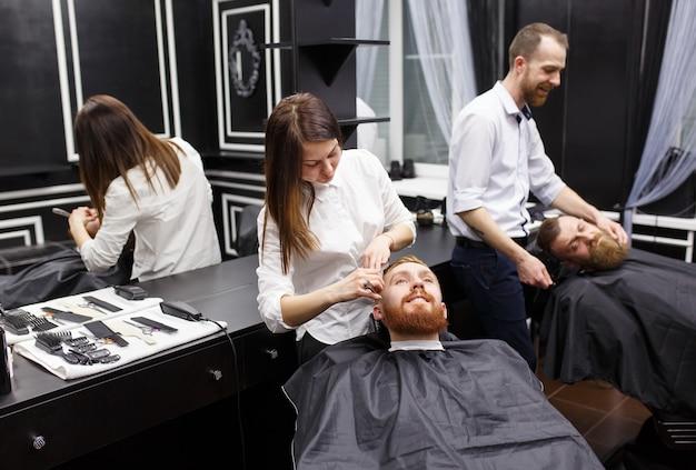 Confiante equipa visitando cabeleireiros na barbearia.