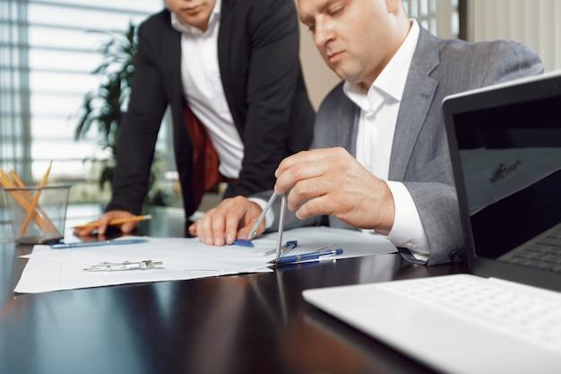 Confiante equipe de engenheiros trabalhando juntos em um estúdio de arquiteto.
