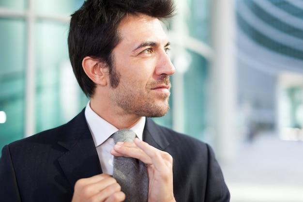 Confiante, homem negócios, ajustar, seu, gravata