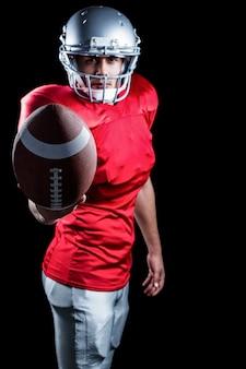 Confiante jogador de futebol americano, mostrando a bola