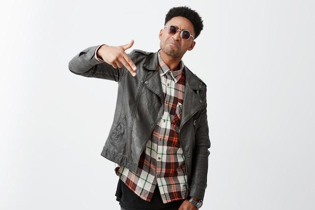 Confiante, jovem atraente pele africana masculina com cabelo encaracolado na jaqueta de couro na moda e óculos de sol, fazendo arma gesto com a mão com expressão do rosto.