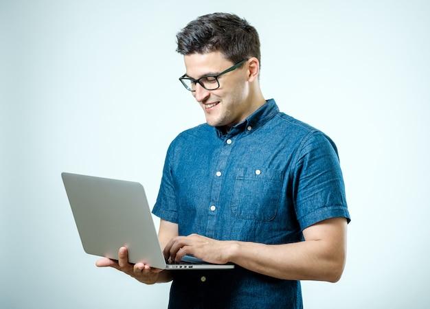 Confiante jovem bonito na camisa segurando laptop