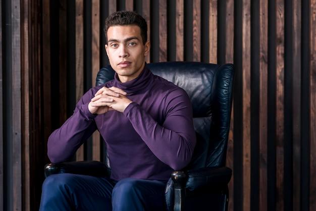 Confiante jovem com a mão entrelaçada sentado na poltrona aconchegante contra a parede de madeira